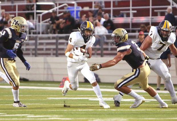 Nevada Union's AJ Meyer (4) finds a gap and picks up yardage for the Miners during first half game play against the Napa Grizzlies.
