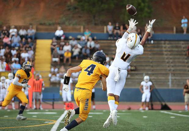Yuba City's Brigham Lessard attempts to pull down a pass during Friday's season opener against the Miners.