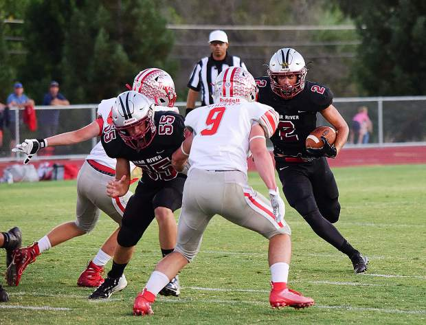 Bear River's Colton Jenkins (2) looks for running room behind teammate Tim Diapoulis (55) during the Bruins' 21-7 victory over Truckee last week. The Bruins hit the road today, traveling to Placerville to face the El Dorado Cougars.