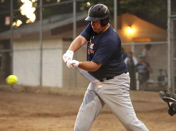 Longs Bottle Shop's Rusty Newnan smashes the ball for a base hit against All Star Auto.
