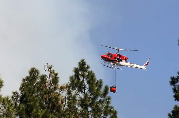 A helitack copter prepares to make a bucket drop onto the Venus Court vegetation fire Thursday afternoon off of Dog Bar Road in Grass Valley.
