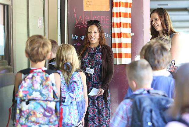 Third graders at Deer Creek Elementary School greet their third grade teacher Vanessa Machado as they walk in to class on the first day of school Wednesday morning in Nevada City.