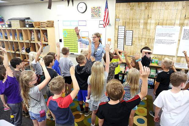 Students in Tracy Green's second grade class raise their right hands before placing them over their hearts to recite the Pledge of Allegiance Wednesday morning in her class at Deer Creek Elementary School.