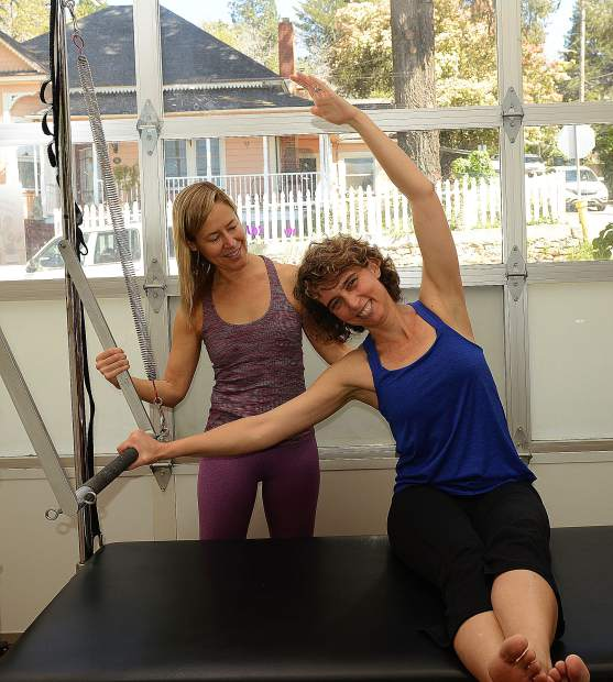 Shannon Casey practices stabilizing her pelvis and strengthening her side body using the Pilates Cadillac Push Through Bar at The Pilates Place in Grass Valley.
