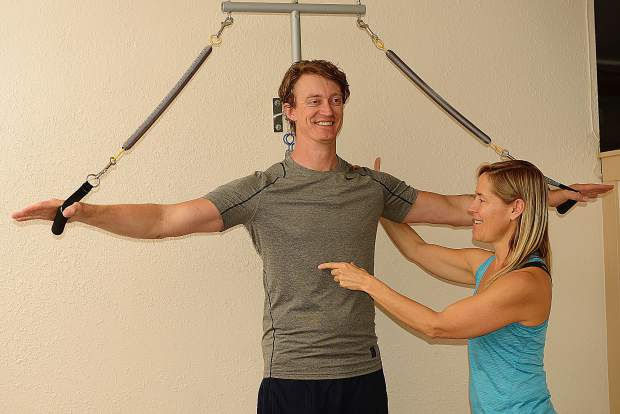 Pilates teacher Justin Shipley shows activating the core, stabilizing through the legs and then engaging his arms. The Ped-o-Pull at The Pilates Place helps connect limbs with torso.