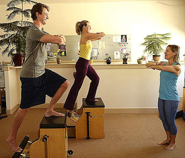 As Justin Shipley, from left, and Kate Flore step up on the Pilates chair at The Pilates Place they are integrating their core with the action of their legs and strengthening the length of their spines.
