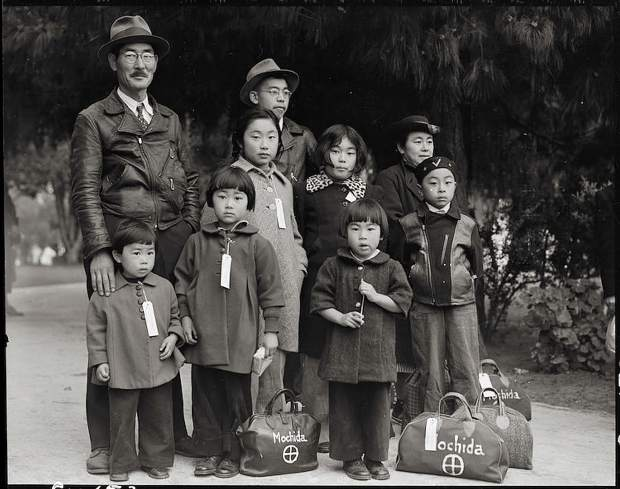 May 8, 1942 — Hayward, California. Members of the Mochida family awaiting evacuation bus. Identification tags are used to aid in keeping the family unit intact during all phases of evacuation. Mochida operated a nursery and five greenhouses on a two-acre site in Eden Township. He raised snapdragons and sweet peas. Evacuees of Japanese ancestry were housed in War Relocation Authority centers during World War II.
