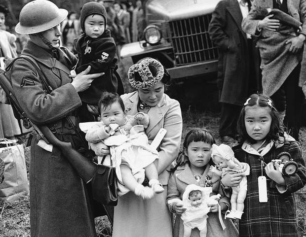 Mrs. Shigeho Kitamoto had no time for tears when she was evacuated along with other Japanese from Bainbridge Island in Washington State, March 30, 1942. She has too busy looking after her four children.  Corporal George Bushy, member of the military guard which supervised the departure of 237 Japanese for California, gave her a hand with the youngest.
