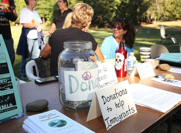 A donation jar to help immigrants sits on a table next to other informational pamphlets.