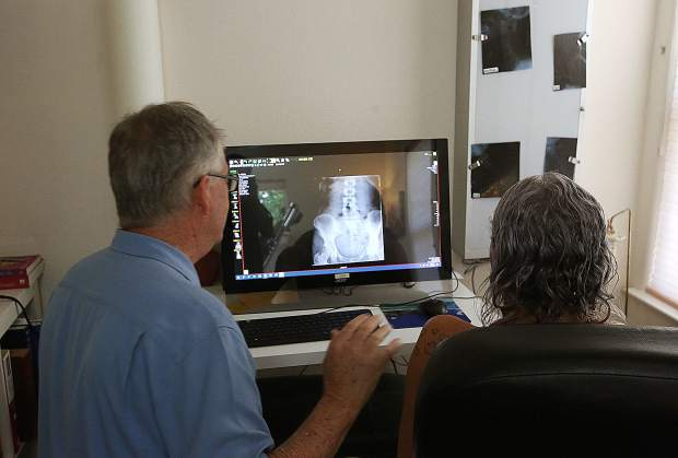 Dr. Dale Jacobson goes over some x-rays with a client at his Nevada City offices off of Gold Flat Road.