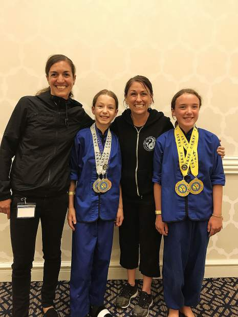 Amelia Regan, second from left, and Kayla Aaron, far right, combined to win two golds, two silvers and a bronze medal at the U.S. International Kuo Shu Championship Tournament held in Hunt Valley, Maryland in late July.