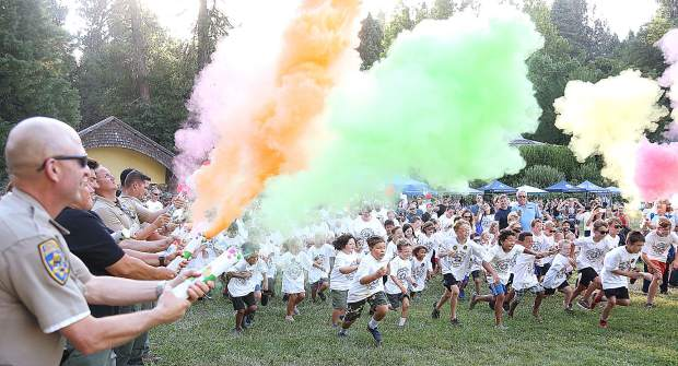 Rows of local law enforcement and fire fighting personnel mark the beginning of the National Night Out color run with an explosion of color Tuesday evening at Pioneer Park.