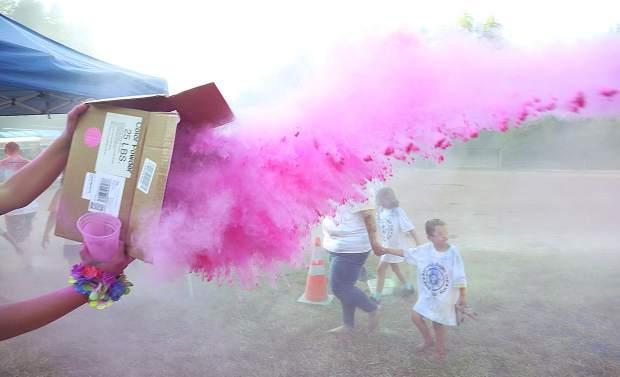 A bright pink swath of powdered color is flung across the color run path.