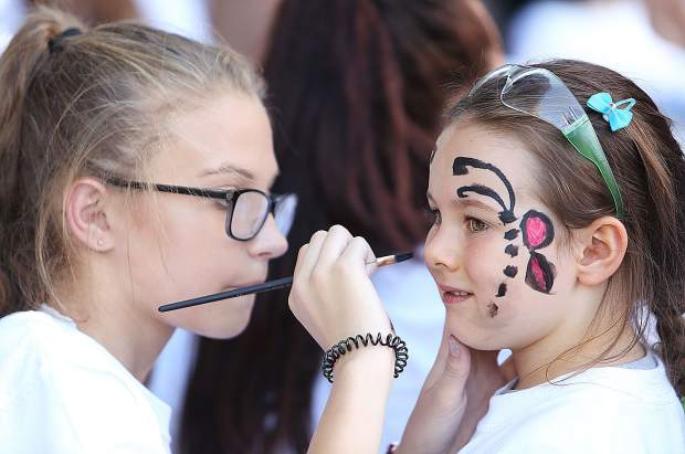 Madison Tullier, 14, paints a butterfly on the face of Haileigh Pasciuti, 5, prior to Tuesday's color run at Pioneer Park.