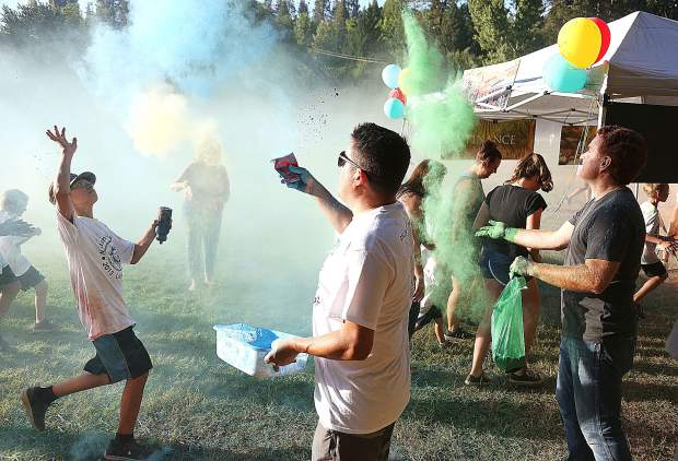 Grass Valley Councilman Ben Aguilar and Grass Valley City Manager Tim Kiser throw blue and green clouds of color at the color run participants Tuesday at Pioneer Park in Nevada City. The event switches annually between the Nevada City location and Grass Valley's DeVere Mautino Park.