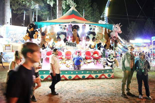A carnival game worker stands at the bucket toss game while fair goers pass by.