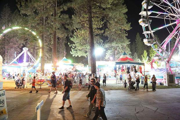 Fair goers walk among the rides and games after the sun goes down at the Nevada County Fair.