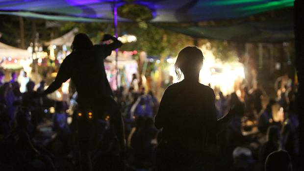 Silhouettes move to the music during Saturday night's lineup of entertainment at Ridgestock.