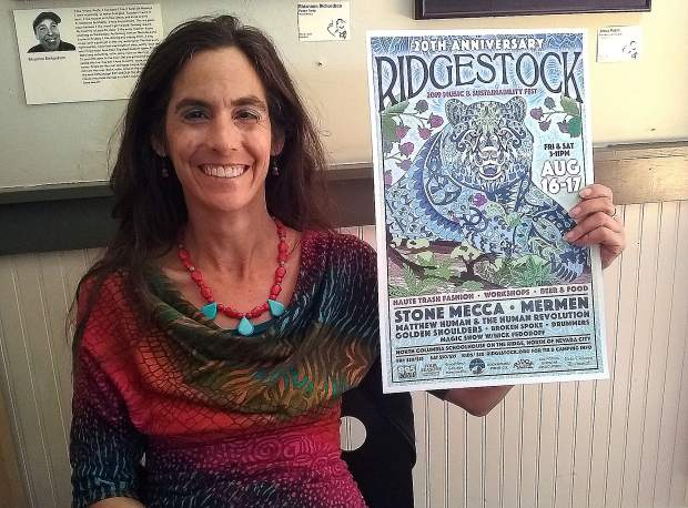 Roo Cantada shows off the poster for the 20th anniversary of Ridgestock.