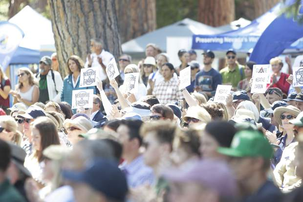 Members of the audience hold signs supporting action against climate change at Tuesday's Lake Tahoe Summit.