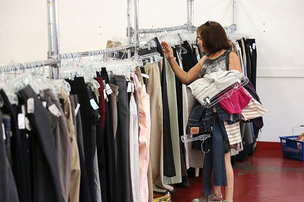 A shopper flips through one of the remaining clothing racks with items for sale Thursday at the Salvation Army Thrift Store in downtown Grass Valley. Clothing items have been reduced to 25 cents each.