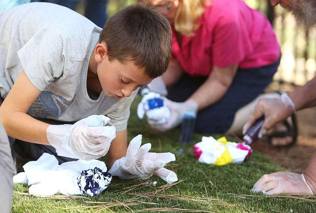 Grass Valley's Taj Daunch-Greenberg, 10, works on his tie dye creation during Thursday's free event at the Madelyn Helling Library.