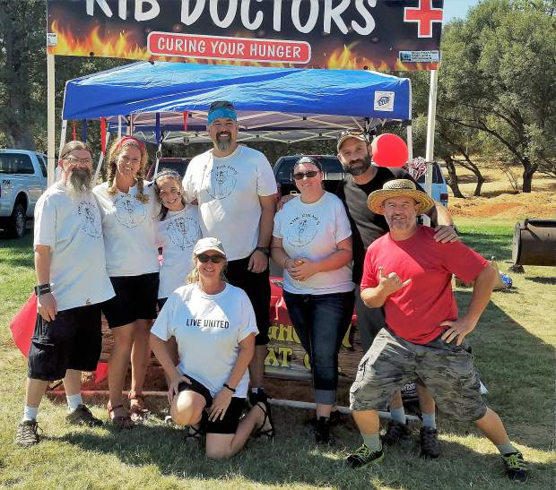 Megan Timpany (kneeling in center), executive director of United Way, poses with Kristian Hockingson (center, back row), and his Backyard BBQ team,
