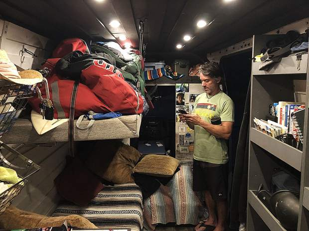 Sean Ross texting in his van. He plans to explore the U.S. over the next two years on the road.