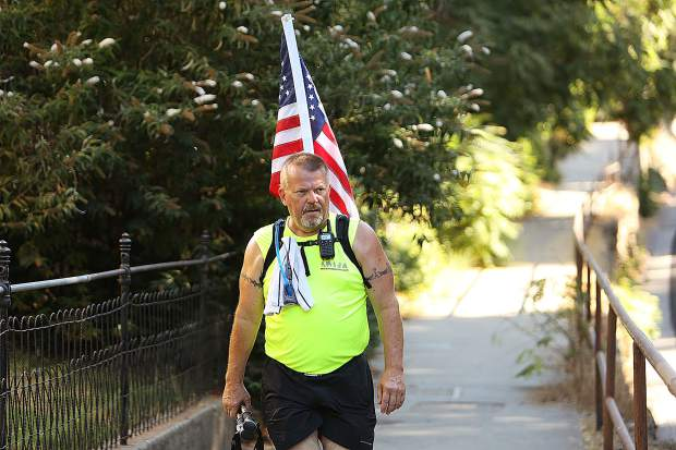 Shannon Poe of the Walk4Liberty makes his way down Mill Street Saturday morning with an American flag strapped to his back.