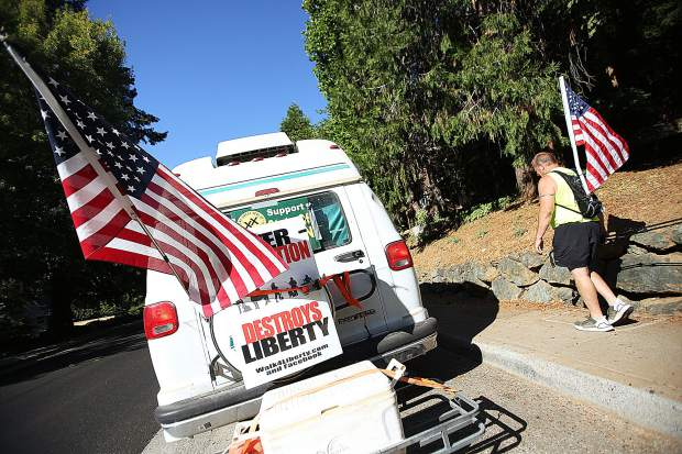 Shannon Poe, one of two walkers in the Walk4Liberty, walks along Mill Street near a support vehicle helping the walkers as they traverse the entirety of Highway 49 to raise awareness about what they call over-regulation by the government.