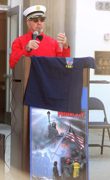 Dressed in historic firefighter attire, retired Nevada County Supervisor and fire chief Hank Weston, recalls the reaction his firefighters had to the 9/11 attacks in 2001. Weston stands behind a shirt that was traded to him from members of FDNY following the attacks on the World Trade Center.