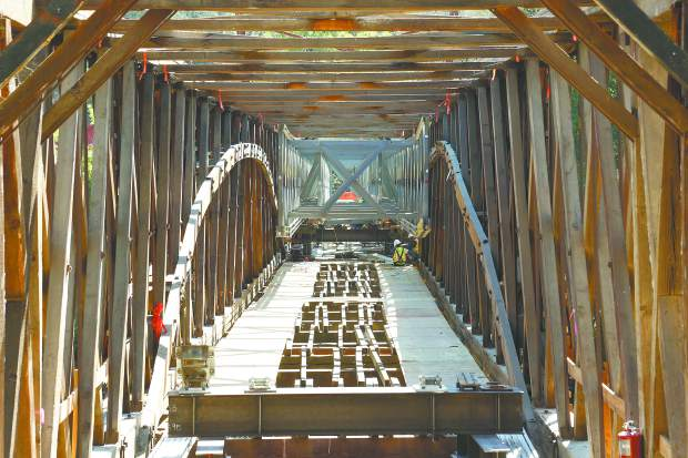 The inner framework of the 1860s Bridgeport historic covered bridge is exposed as workers from Spectra Contractors out of Pomona work to install metal supports that will allow the bridge to be safely raised to the height desired for the restoration.