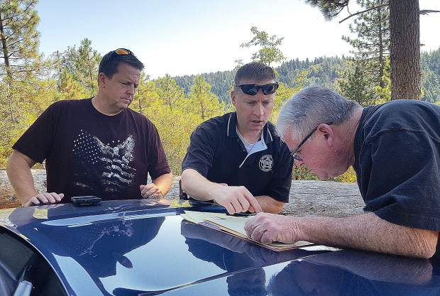 Philip Desmet, left, and Charles Millar, right, pore over a hand-drawn map that shows where Millar found a skull fragment in 1993. The two men accompanied Nevada County Sheriff's Lt. Bob Jakobs, center, to the site earlier this month, after the skull cap was linked to Desmet's birth mother, Joanne Dolly Burmer, who disappeared in 1973.