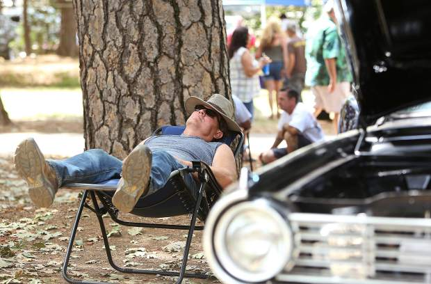 A car owner takes a nap next to his vehicle on display under the pines at the Nevada County Fairgrounds during last weekends' Roamin Angels car show.