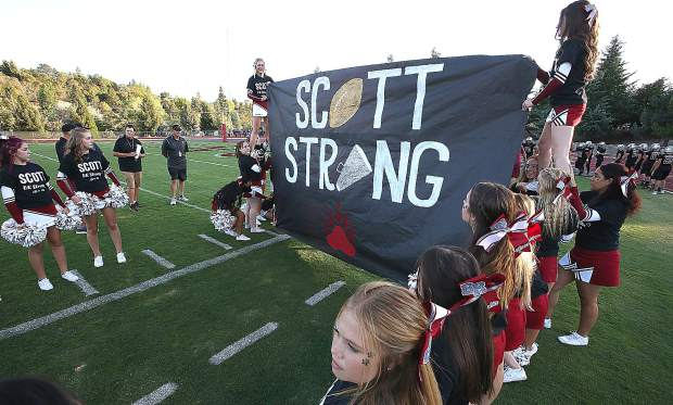 The Bear River cheer squad wears shirts and hold up a sign honoring Paul Scott, a Bear River parent, who died unexpectedly.