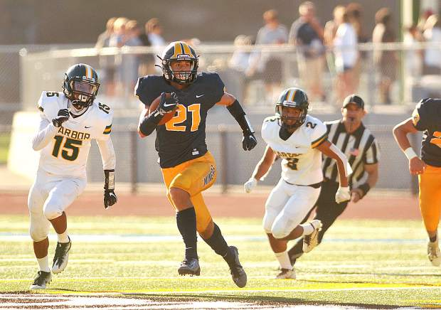 Nevada Union's Jaxon Horne (21) breaks away from the Harbor High School defense during Saturday's blowout win over the Pirates in Santa Cruz.