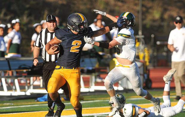 Nevada Union quarterback Gabriel Baker straight arms a Harbor defender during Saturday's 73-0 win in Santa Cruz.