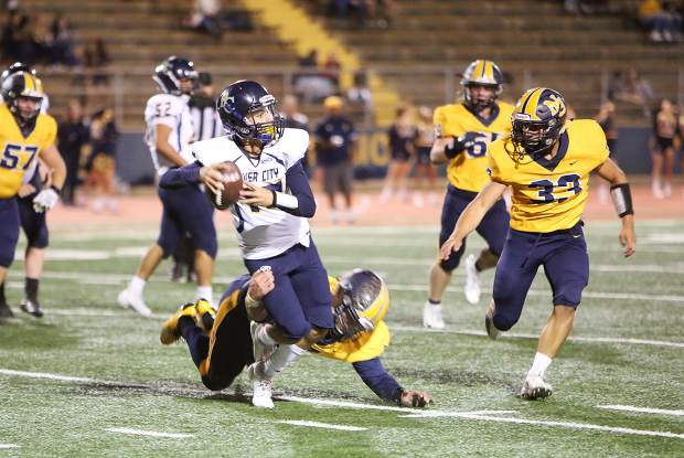 Nevada Union defenders Matthew Dal bon (7) and Duke Morales (33) force River City quarterback to get rid of the ball behind the line of scrimmage during Friday's home win over the visiting Raiders.
