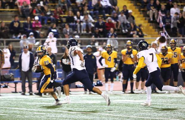 Nevada Union ball carrier Santino Sanchez-Lane (20) runs the ball towards the end zone during the Miners' 63 - 6 win over the River City Raiders.