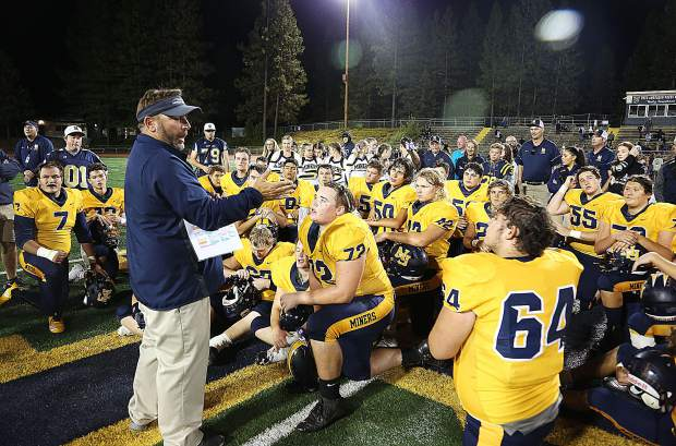 Nevada Union varsity head coach Brad Sparks congratulates his team on another victory mid field at Hooper Stadium following their rout of River City.