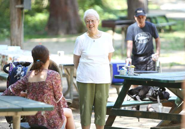 Sierra Roots' Janice O'Brien talks to people during Thursday's lunch program at the Pioneer Park picnic area.