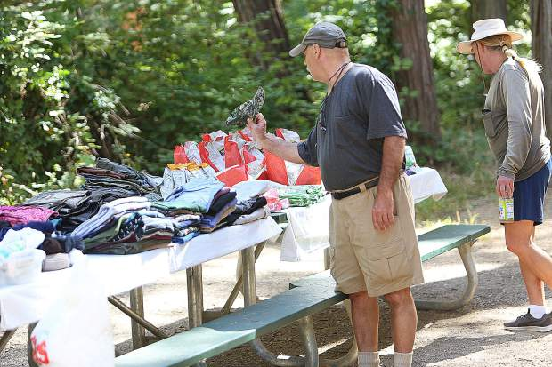 People inspect the items to be given away prior to the 11 a.m. lunch time Thursday at Pioneer Park. 'It's the one time a week when everyone is together,' Ron Custer said. 'They go above and beyond the call of duty. It's hard work and they bring it together.'