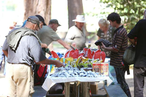About 20 area homeless people help themselves to a table full of supplies such as food, clothing and toiletries set out for them every Thursday at Pioneer Park by members of Sierra Roots as part of their summer lunch program.