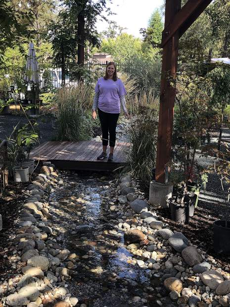 Manager Feona Nowak stands on a bridge over the creek that flows through the yard at Wildflower Nursery Garden and Gift Shoppe.