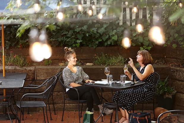 A pair of women share a glass of wine while waiting for their meal among the mood lighting of One 11 Kitchen & Bar's outdoor patio.