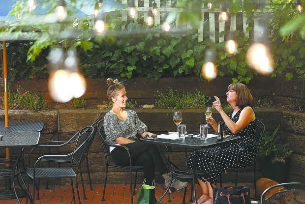 A pair of women share a glass of wine while waiting for their meal among the mood lighting of the One 11 Kitchen and Bar outdoor patio.
