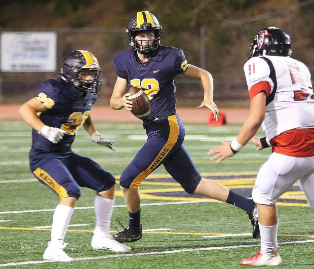 Nevada Union quarterback J.T. Conway (12) pulls back before throwing one of his passes for the night during the Miners' 64-0 rout of the Fairfield Miners.