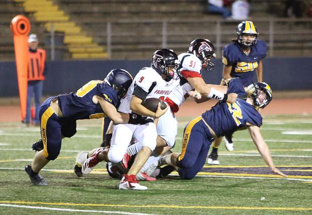 Nevada Union defender Jon Patterson (69) puts the pressure on Fairfield ball carrier Ike Makanani (9) during Friday's win over the Falcons.