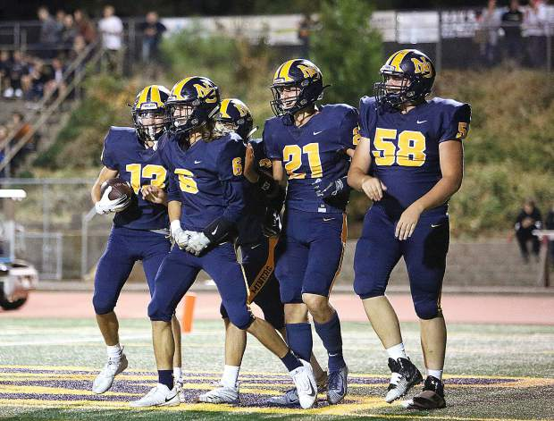 A group of Miners celebrate following a Miners touchdown Friday at Hooper Stadium.