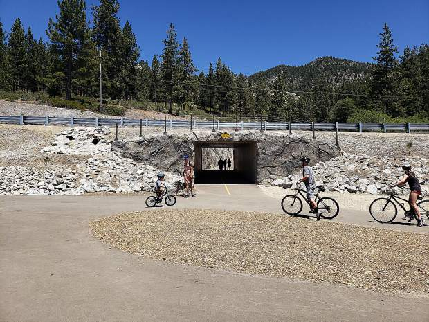 Hikers and bicyclists make their way through the underpass along the Tahoe East Shore Trail.